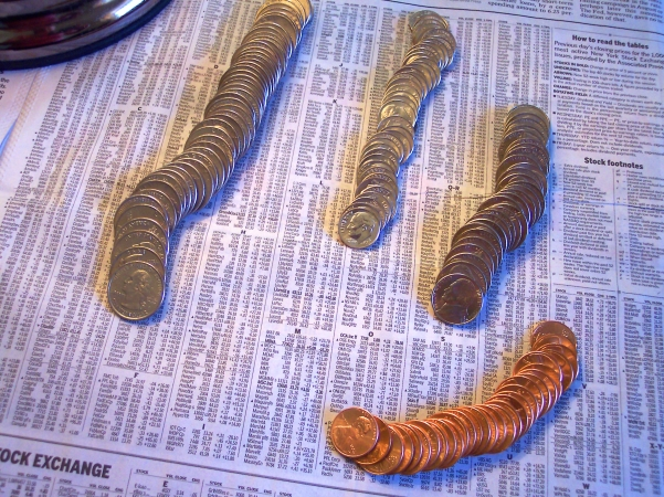 Picture of coins on the stock sheet of anonymous female investors.