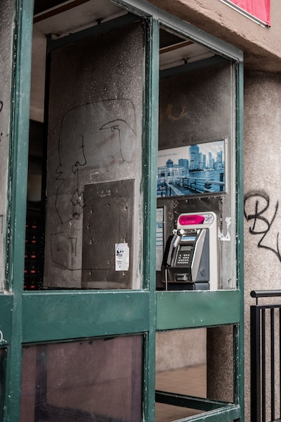Picture of a phone booth wiuth grafitti on it.